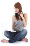 Adolescente feliz con los auriculares y la sentada de la computadora portátil Imagenes de archivo