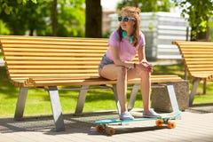 Adolescente feliz con los auriculares y longboard Foto de archivo