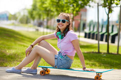 Adolescente feliz con los auriculares y longboard Fotos de archivo libres de regalías
