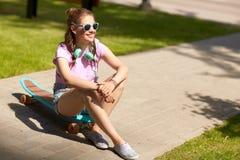 Adolescente feliz con los auriculares y longboard Fotos de archivo