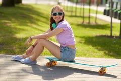 Adolescente feliz con los auriculares y longboard Imágenes de archivo libres de regalías