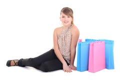Adolescente feliz con los bolsos de compras sobre blanco Imagen de archivo