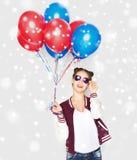 Adolescente feliz con los globos del helio sobre nieve Fotografía de archivo