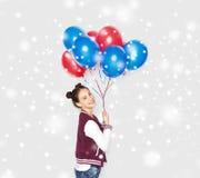 Adolescente feliz con los globos del helio sobre nieve Fotos de archivo