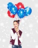Adolescente feliz con los globos del helio sobre nieve Foto de archivo