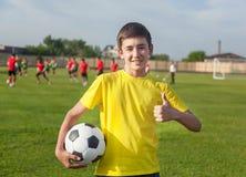 Adolescente feliz con un balón de fútbol en su mano contra el CCB Fotos de archivo libres de regalías