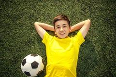 Adolescente feliz con un balón de fútbol que miente en el césped verde Sh Imagen de archivo