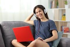 Adolescente feliz con un ordenador portátil y los auriculares que miran la cámara Fotografía de archivo