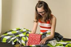 Adolescente feliz con una caja de regalo en casa que se sienta en cama Foto de archivo