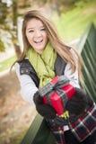 Adolescente feliz da el regalo envuelto con el arco afuera Imagenes de archivo