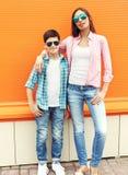 Adolescente feliz de la madre y del hijo que lleva una camisa a cuadros y las gafas de sol Fotografía de archivo