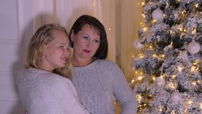 Adolescente feliz de la madre y de la hija que presenta en fondo del árbol de navidad en hogar almacen de video