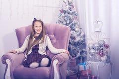 Adolescente feliz de la muchacha delante de un árbol de navidad Imagenes de archivo