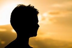 Adolescente feliz de la silueta durante puesta del sol Imagen de archivo