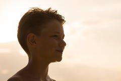 Adolescente feliz de la silueta durante puesta del sol Fotografía de archivo libre de regalías