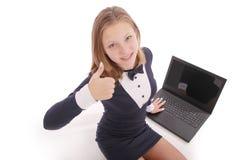 Adolescente feliz del estudiante con el ordenador portátil El sentarse de lado y detener el pulgar Imagen de archivo libre de regalías