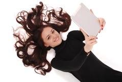 Adolescente feliz del estudiante que miente en el piso con PC de la tableta Imagen de archivo libre de regalías