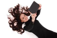 Adolescente feliz del estudiante que miente en el piso que mira la tableta Fotos de archivo libres de regalías