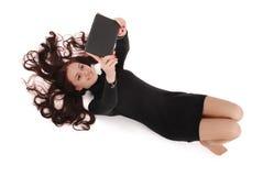 Adolescente feliz del estudiante que miente en el piso que mira la tableta Imagen de archivo libre de regalías