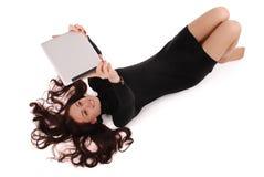 Adolescente feliz del estudiante que miente en el piso que mira la tableta Foto de archivo