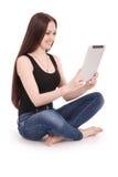Adolescente feliz del estudiante que se sienta de lado en el piso con TA Imagen de archivo libre de regalías