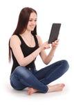 Adolescente feliz del estudiante que se sienta de lado en el piso con TA Imágenes de archivo libres de regalías