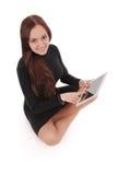 Adolescente feliz del estudiante que se sienta en el piso con PC de la tableta Foto de archivo libre de regalías