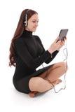 Adolescente feliz del estudiante que se sienta en el piso con PC de la tableta Imagen de archivo