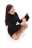 Adolescente feliz del estudiante que se sienta en el piso con PC de la tableta Imágenes de archivo libres de regalías