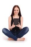 Adolescente feliz del estudiante que se sienta en el piso con PC de la tableta Fotos de archivo libres de regalías