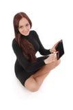 Adolescente feliz del estudiante que se sienta en el piso con PC de la tableta Imagen de archivo libre de regalías