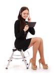 Adolescente feliz del estudiante que se sienta en la escalera que mira el tabl Foto de archivo