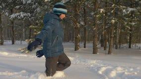 Adolescente feliz del muchacho que camina a través de la nieve acumulada por la ventisca en actividad del invierno del bosque del metrajes