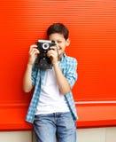 Adolescente feliz del niño pequeño con la cámara retra del vintage en ciudad Fotografía de archivo libre de regalías