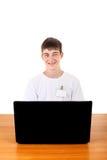 Adolescente feliz detrás del ordenador portátil Fotografía de archivo