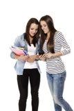 Adolescente feliz dos que mira un smartphone Fotos de archivo