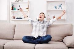 Adolescente feliz en auriculares con el móvil en casa Fotografía de archivo