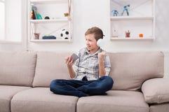 Adolescente feliz en auriculares con el móvil en casa Imagen de archivo libre de regalías