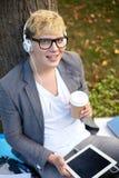 Adolescente feliz en auriculares con PC de la tableta Fotos de archivo libres de regalías