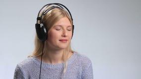 Adolescente feliz en auriculares sobre blanco almacen de video
