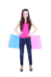 Adolescente feliz en camiseta rosada con los bolsos de compras Imágenes de archivo libres de regalías