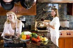 Adolescente feliz en cocina con la madre Foto de archivo