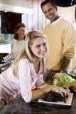 Adolescente feliz en cocina con los padres Fotografía de archivo