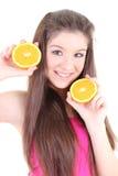 Adolescente feliz en color de rosa con la mitad de naranjas Fotos de archivo