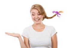 Adolescente feliz en el pelo de la trenza que presenta la mano Fotos de archivo