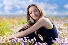 Adolescente feliz en el prado con las flores Imagen de archivo