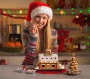 Adolescente feliz en el sombrero de santa con la casa de la galleta de la Navidad Fotografía de archivo libre de regalías