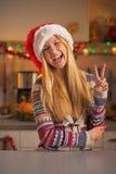 Adolescente feliz en el sombrero de santa que muestra gesto de la victoria Imágenes de archivo libres de regalías