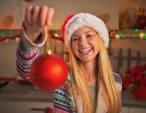 Adolescente feliz en el sombrero de santa que muestra la bola de la Navidad Fotos de archivo libres de regalías