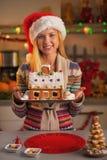 Adolescente feliz en el sombrero de santa que muestra la casa de la galleta de la Navidad Fotos de archivo libres de regalías